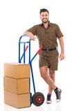 Courier posing with a push cart Royalty Free Stock Photos