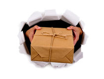Courier or postman hands delivering or giving small parcel through torn white paper background Royalty Free Stock Photos