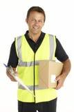 Courier retenant un colis et une planchette photo libre de droits