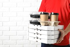 Courier with stack of orders near white brick wall, space for text. Food delivery service royalty free stock photos