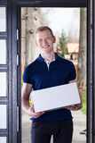 Courier standing with box in house door royalty free stock photos