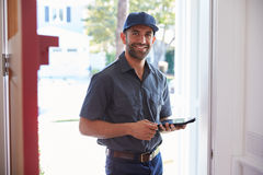 Courier Standing At Front Door With Digital Tablet Royalty Free Stock Photos