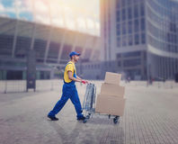 Courier with trolley in city, logistic service. Male courier with trolley in city. Distribution business. Cargo delivery. Empty, clear containers. Logistic and Royalty Free Stock Photography