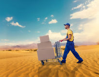 Courier with trolley in desert, cargo delivery. Male courier with trolley in desert. Distribution business. Cargo delivery. Empty, clear containers. Logistic stock image