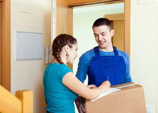 Courier in uniform brought package to girl at home Stock Images