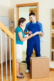 Courier in uniform brought package to housewife Royalty Free Stock Image