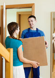 Courier in uniform brought package to woman Royalty Free Stock Photography