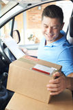 Courier In Van Delivering Package To Domestic House Stock Image