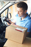 Courier In Van Delivering Package To Domestic House Stock Photo