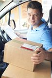 Courier In Van Delivering Package To House royalty free stock photo