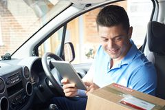 Courier In Van With Digital Tablet Delivering Package To House royalty free stock photo