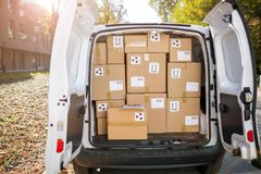 Courier van full of parcels and boxes. Open courier van full of parcels and boxes royalty free stock photography