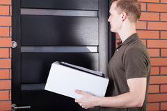 The courier waiting outside the door. Of the box and documents Stock Photo