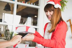 Courier wearing santa claus hat delivering a parcel box to custo Stock Images