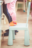 Courious little girl standing on the little chair. Little girl standing on the chair to reach the top of a kitchen desk stock image