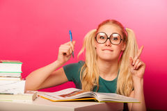 Courious, playful schoolgirl with two hair tails sitting on floor behind the small table full of books smiling, excited to got. Courious, playful schoolgirl with royalty free stock photography