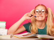 Courious, playful schoolgirl with two hair tails sitting on floor behind the small table full of books smiling, excited to learn. Courious, playful schoolgirl royalty free stock image