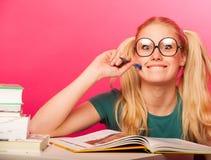 Courious, scolara allegra con due code dei capelli che si siedono sul floo Immagine Stock Libera da Diritti