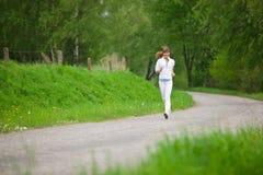Courir - femme folâtre exécutant sur la route en nature Images libres de droits