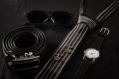 Couro, óculos de sol, laço, botão de punho, relógio em um backgroun preto Imagens de Stock Royalty Free