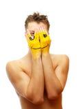 Couro cru do homem sua face sob a máscara do sorriso Fotos de Stock Royalty Free