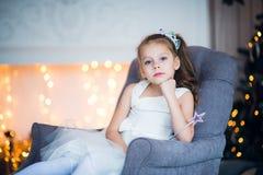 Couronne de port gaie heureuse de petite fille excitée au réveillon de Noël, se reposant sous l'arbre lumineux décoré salutation photos stock