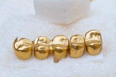 Couronnes dentaires d'or sur le sucre photographie stock libre de droits