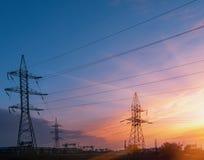 Courrier à haute tension, fond à haute tension de coucher du soleil de ciel de tour Image libre de droits