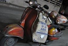 Courrier падает продукты на магазин, его Vespa припаркованный на улице в Бангкоке в марте 2011 стоковое изображение rf