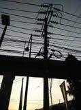Courrier de l'électricité contre le sillhouette Photographie stock libre de droits