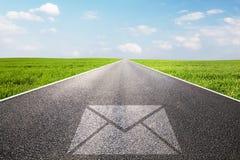 Courrier, symbole de message sur la longue route droite, route Photo stock