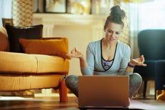 Cours de observation de yoga de femme de sports sur l'Internet par l'intermédiaire de l'ordinateur portable photographie stock