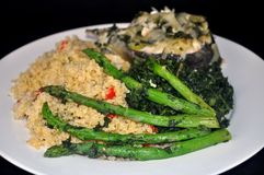 Course. This is a picture of a plate with cooked fish, Quinoa, asparagus and spinach Stock Image