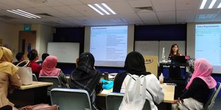 Course briefing. Workshop participants listening to a presenter speaking in front of a classroom in a professional educational institute in singapore stock image