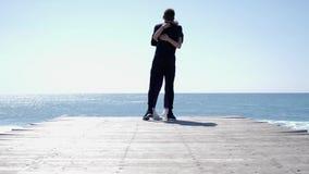 Course caucasienne convenable d'homme et de femme de jeunes ensemble vers la mer tenant des mains et ?treindre Mouvement lent banque de vidéos