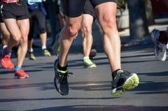 Course courante de marathon, pieds de personnes sur la route Photographie stock