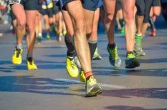 Course courante de marathon, pieds de personnes sur la route Image stock