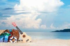 Course d'été Bikini et bascules, chapeau, et sac près de chaise de plage sur la plage sablonneuse contre la mer et le ciel bleus photo stock