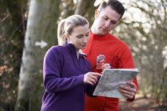 Course d'orientation de couples dans les régions boisées avec la carte et la boussole Image stock