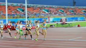 Course de groupe d'athlètes de femmes sur la voie contre des supports de spectateurs banque de vidéos
