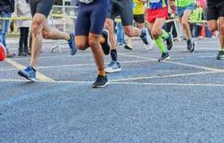 Course de marathon, pieds de personnes courant sur la route urbaine photos stock