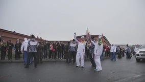 Course de relais de torche olympique de Sotchi dans le St Petersbourg Flamme de passage de porteur de flambeau à l'autre Mains de banque de vidéos