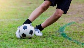 Course de vitesse de footballeur de garçon pour tirer la boule au but sur l'herbe verte photos libres de droits