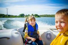 Course des enfants sur l'eau dans le bateau Photo libre de droits