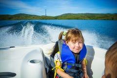 Course des enfants sur l'eau dans le bateau Photographie stock