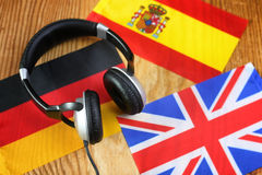 Course language headphone and flag on a table. Language course headphone and flag on wooden table Royalty Free Stock Photo