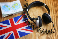 Course language headphone and flag on a table. Language course headphone and flag on wooden table Royalty Free Stock Image