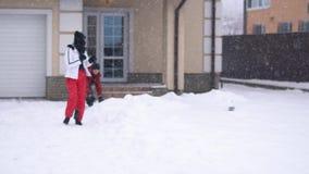 Course mignonne d'homme et de femme hors de la maison dans l'arrière-cour Un homme saisit la neige et des jets à la fille, elle c banque de vidéos