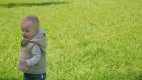 Courses blondes d'enfant en bas âge sur l'herbe verte Vue de mouvement lent banque de vidéos