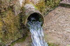 Courses d'eau douce hors d'un tuyau d'acier photo libre de droits